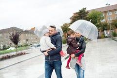 Jonge familie met twee dochters onder de paraplu's, stad Royalty-vrije Stock Fotografie