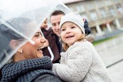 Jonge familie met twee dochters onder de paraplu's, stad Royalty-vrije Stock Afbeelding