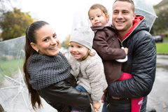 Jonge familie met twee dochters onder de paraplu's, stad Stock Foto