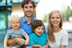 Jonge familie met twee jonge geitjes Royalty-vrije Stock Afbeeldingen