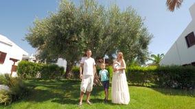 Jonge familie met twee kinderen dichtbij olijfboom in de tuin stock video