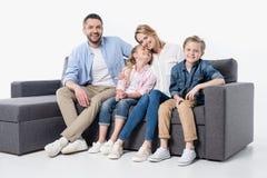 Jonge familie met twee kinderen die samen op laag zitten die op wit wordt geïsoleerd stock fotografie