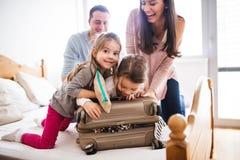 Jonge familie met twee kinderen die voor vakantie inpakken stock afbeelding