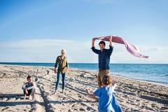 Jonge familie met twee kleine kinderen die in openlucht op strand lopen royalty-vrije stock foto