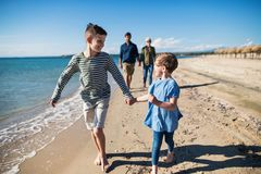 Jonge familie met twee kleine kinderen die in openlucht op strand lopen royalty-vrije stock fotografie