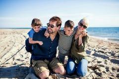 Jonge familie met twee kleine kinderen die in openlucht op strand zitten stock afbeeldingen