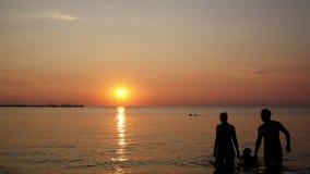 Jonge familie op het strand onder een kleurrijke zonsondergang stock videobeelden