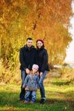 Jonge familie, ouders met kleine kinderen in het gouden park van de de herfststad stock afbeeldingen