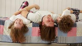 Jonge familie - vader en zijn kinderen die op het bed spelen stock footage
