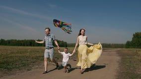 Jonge familie van drie mensen die pret met hun zoon hebben Zij stellen en vliegen een kleurrijke vlieger in werking stock footage