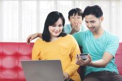 Jonge familie van echtgenoot, zwangere vrouw en peuter die online winkelen stock foto