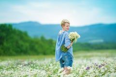 Jonge familie van mooie damemoeder en leuk dochtermeisje die met blonde krullende haren op het purpere bloemengebied dragen lopen royalty-vrije stock afbeeldingen