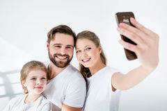 Jonge familie in witte t-shirts die selfie met smartphone in studio nemen stock fotografie