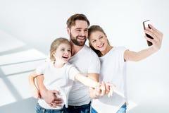 Jonge familie in witte t-shirts die selfie met smartphone in studio nemen stock afbeeldingen