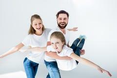 Jonge familie in witte t-shirts en jeans die pret hebben samen stock afbeelding