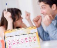 Jonge familie in zwangerschap planningsconcept met ovulatie calend stock afbeelding