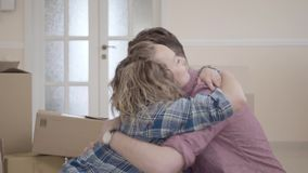 Jonge familieomhelzingen die in lichte ruimte met dozen op de achtergrond zitten man en vrouw die samen lachen Gehuwd paar stock video