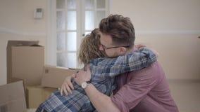 Jonge familiezitting in lichte ruimte met dozen op de achtergrond Man die sleutel tonen aan vrouw, rekt zij uit hand uit en stock footage