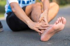 Jonge fitness mens die zijn verwonding van het sportenbeen houden spier pijnlijk tijdens opleiding Aziatische agent die enkelpijn stock foto