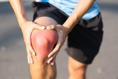 Jonge fitness mens die zijn verwonding van het sportenbeen houden spier pijnlijk tijdens opleiding Aziatische agent die kniepijn  royalty-vrije stock fotografie