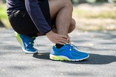 Jonge fitness mens die zijn verwonding van het sportenbeen, spier houden pijnlijk tijdens opleiding Aziatische agent die kalfspij stock fotografie
