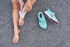 Jonge fitness vrouw die zijn verwonding van het sportenbeen na het lopen houden stock foto's