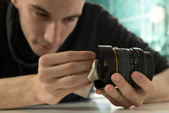 Jonge fotograaf die lens controleren Stock Fotografie