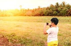 Jonge fotograaf die zonsondergangfoto's schieten royalty-vrije stock afbeeldingen