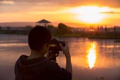 Jonge fotograaf en Reflexcamera op driepoot dichtbij de lagune royalty-vrije stock afbeeldingen