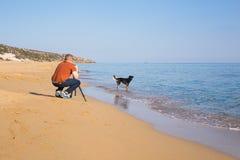 Jonge fotograaf en videographer het maken van foto's en video's van overzees en zijn hond met de camera op een driepoot stock afbeeldingen