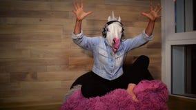 Jonge freaky vrouw in grappig eenhoornmasker stock video