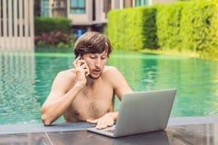 Jonge freelancer die aan vakantie naast het zwembad werken Stock Foto