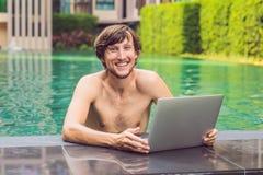 Jonge freelancer die aan vakantie naast het zwembad werken Stock Afbeeldingen