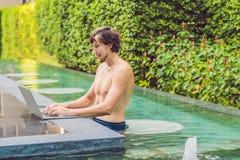 Jonge freelancer die aan vakantie naast het zwembad werken Stock Fotografie