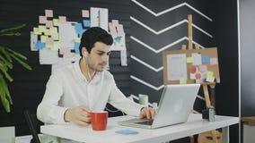 Jonge freelancer in vrijetijdskleding die in bureau werken Het spreken over Skype aan klant stock videobeelden
