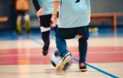 Jonge futsal spelers en voetbalbal met motieonduidelijk beeld Binnen futsal voetballers in motie die futsal gelijke spelen royalty-vrije stock foto's