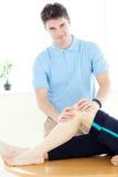 Jonge fysiotherapeut die een beenmassage geeft Royalty-vrije Stock Fotografie