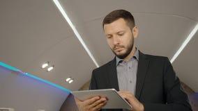 Jonge gebaarde advocaatzakenman in het werk proces, die tablet in persoonlijk vliegtuig gebruiken ondernemersstraal stock video