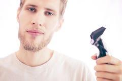 Jonge gebaarde knappe die kapper met het scheren machine op een witte achtergrond wordt geïsoleerd stock afbeeldingen