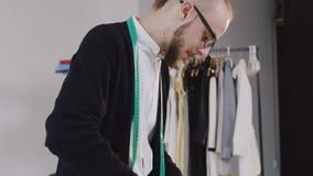 Jonge gebaarde manierontwerper met meetlint op zijn hals die zich in kleermakerijstudio en besnoeiing met schaar een patroon bevi stock video