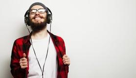 jonge gebaarde mens die aan muziek luisteren Stock Fotografie