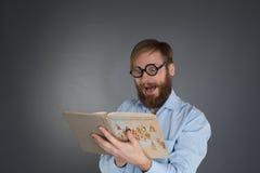 Jonge gebaarde mens die glazen dragen die een boek lezen Royalty-vrije Stock Afbeelding