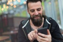 Jonge gebaarde mens die mobiele telefoon met behulp van Royalty-vrije Stock Fotografie