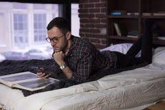 Jonge gebaarde mens die op bed liggen en smartphone gebruiken Stock Afbeeldingen
