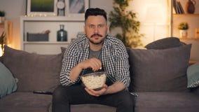 Jonge gebaarde mens die op TV letten en popcorn eten die thuis op laag zitten stock footage