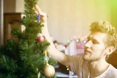 Jonge gebaarde mens die thuis binnenlandse voorbereiding doen aan het de vakantieconcept F van het Kerstmis nieuwe jaar stock afbeelding