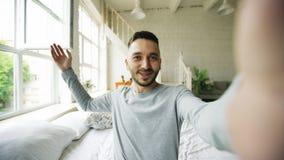 Jonge gebaarde mens die thuis tabletcomputer met behulp van die videopraatjezitting in bed hebben Royalty-vrije Stock Fotografie