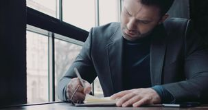 Jonge gebaarde mens in een formele uitrusting die de ideeën op het document in een café neerschrijven Zijnd de werkgever succesv stock video