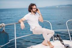 Jonge gebaarde mens op een luxejacht met een prachtige mening van het overzees royalty-vrije stock afbeelding