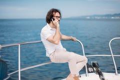 Jonge gebaarde mens op een luxejacht met een prachtige mening van het overzees royalty-vrije stock afbeeldingen